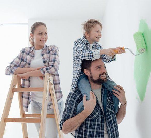 szczęśliwa rodzina, mama nadrabinie, tata trzyma małego chłopca naplecach którymaluje białą ścianę, mieszkanie +