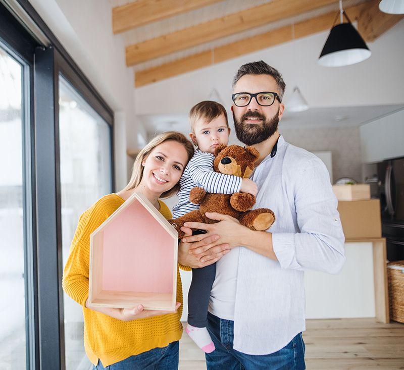 trzy osobowa rodzina, tata trzyma małe dziecko narękach które trzyma misia, mama przytula się dodziecka itrzyma wrękach pudełko wkształcie wdomu, mieszkanie+