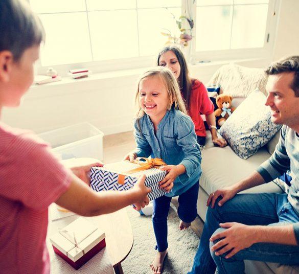 szczęśliwa 4 osobowa rodzina, dwójka dzieci dających sobie prezent, mieszkanie +