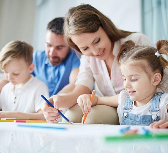 szczęśliwa rodzina, napierwszym palnie mama rysuje kredkami zcórką, nadrugim planie tata rysuje zsynem, mieszkanie +