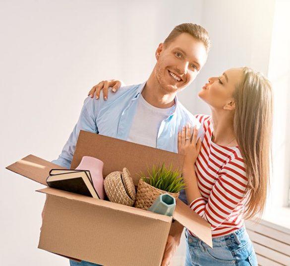 dwójka młodych ludzi, wprowadzają się domieszkania, dziewczyna daje całusa chłopakowi, chłopak trzyma wręku kartonowe pudło, mieszkanie+