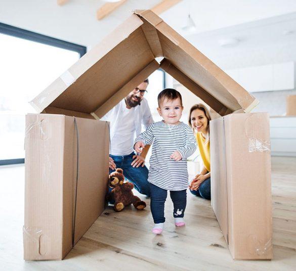 szczęśliwa rodzina, mama, tata, małe dziecko, rodzice wtle patrzą nadziecko które przechodzi przezdom zrobiony zkartonów, mieszkanie +