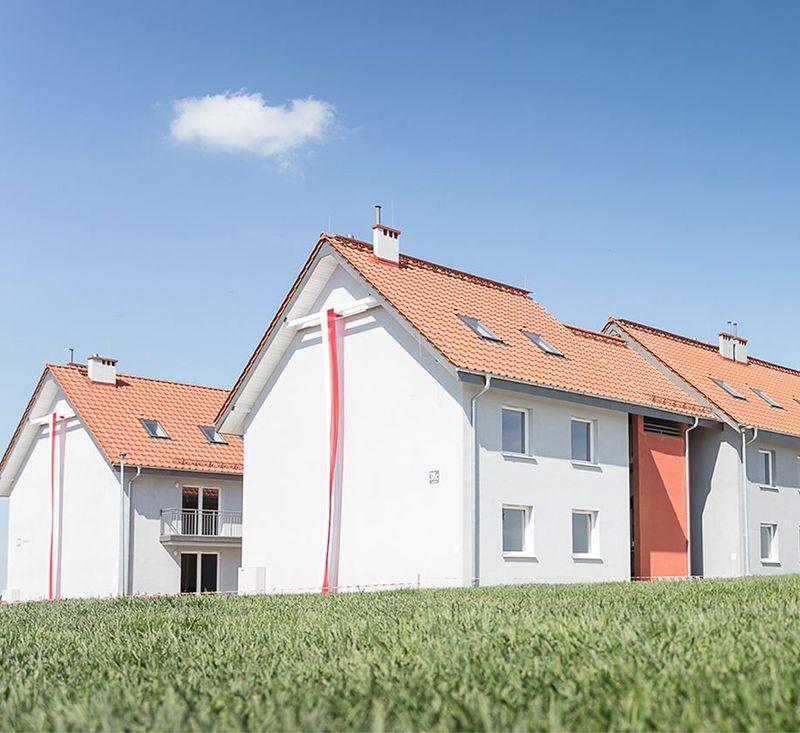 piętrowe szeregowe domy zczerwonym dachem natle niebieskiego nieba, naścianie domu wisi biało czerwono flaga, mieszkanie+
