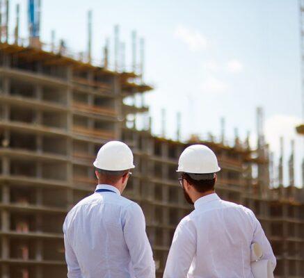 dwójka inżynierów w białych koszulach i białych kaskach przygląda się budowie w tyle, mieszkanie plus