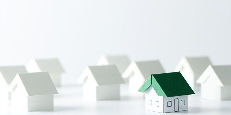 domek z papieru z zielonym dachem na tle papierowych białych domków, mieszkanie+