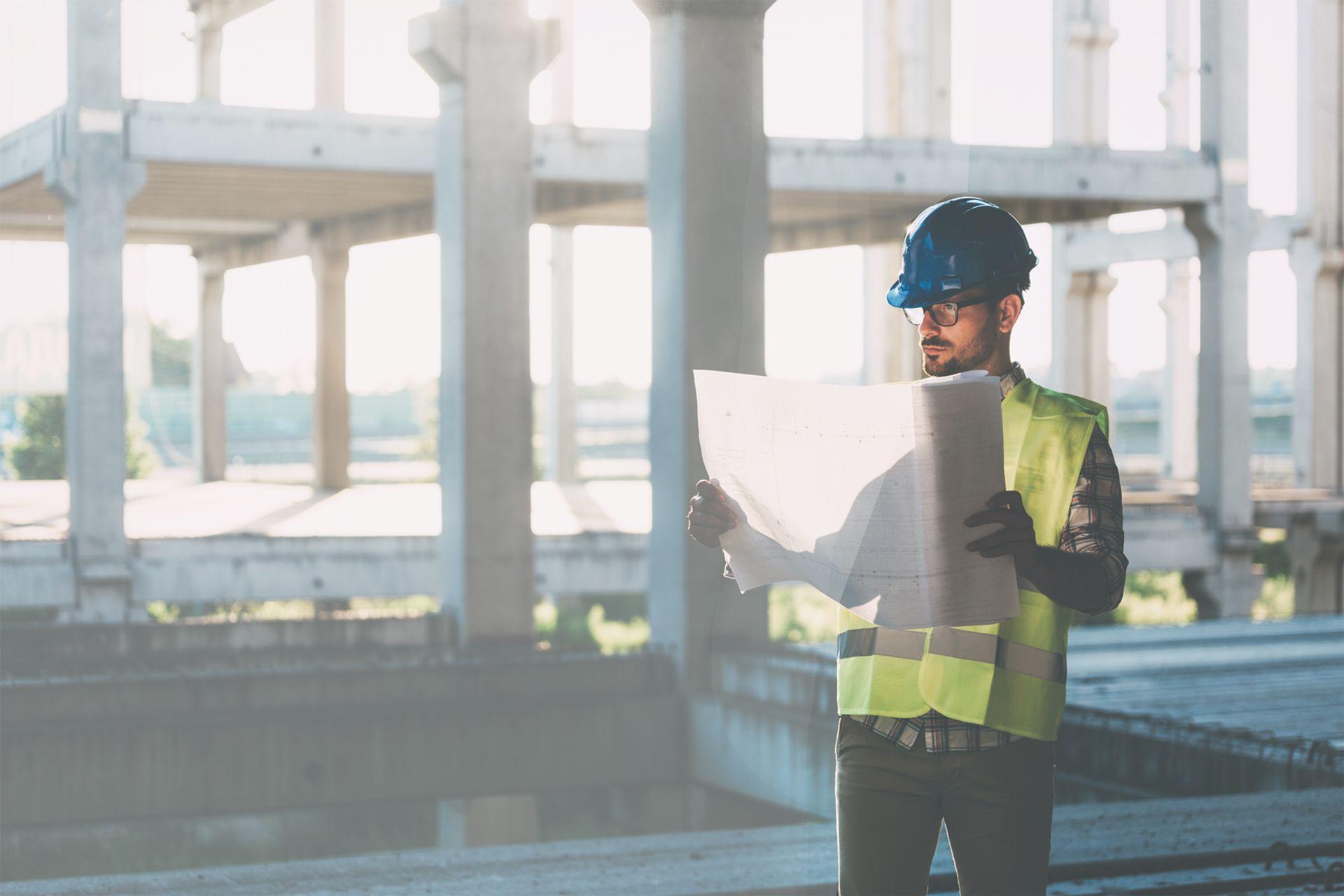 budowa, pracownik budowlany trzyma wręku plan budowy, pracownik wkasku iwżółtej kamizelce, mieszkanie +