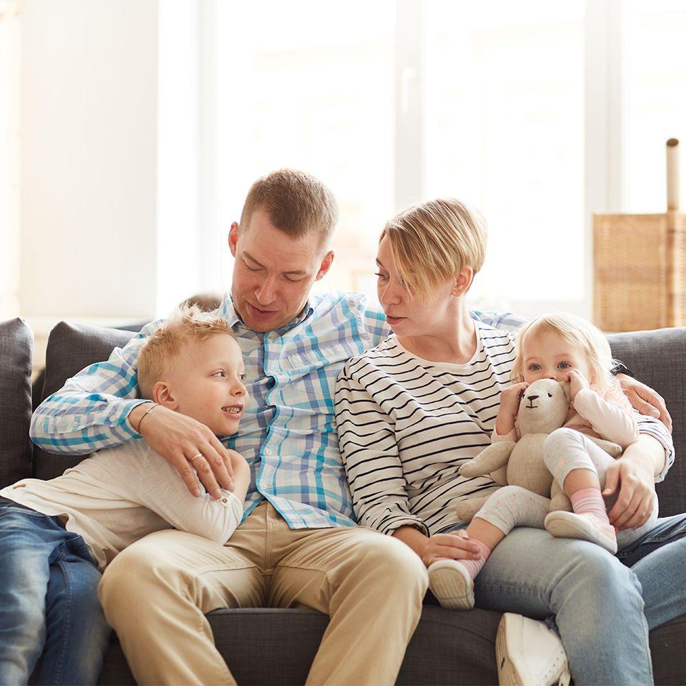 szczęśliwa rodzina mama tata dwójka dzieci siedzą nakanapie